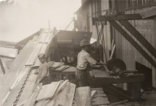 """""""Dangerous work. Charlie McBride. This twelve-year-old boy has a steady job with the Miller & Vidor Lumber Company. He takes slabs out of the chute which has a moving endless chain to carry the wood up the chute. He passes the slabs onto other boy who saws them on an unguarded circular saw. Charlie runs the saw himself whenever he gets the chance. He is exposed not only to the above dangers, but to the weather. No roof even. Has been here for some months. 'Get four bits a day.' (fifty cents) Works ten hours."""" — from Hine's field notes, 1913"""