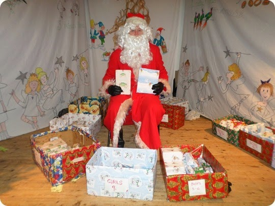 Father Christmas waits to give presents to a boy and girl
