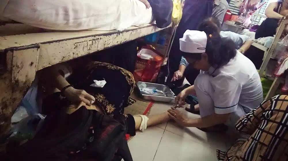 Bệnh viện Ung bướu TP.HCM: Nhân viên y tế điều trị cho bệnh nhân nằm dưới gầm giường.