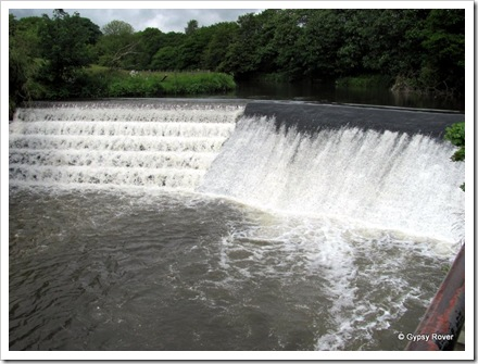 The river Irwell which is flowing quite fast over this weir.