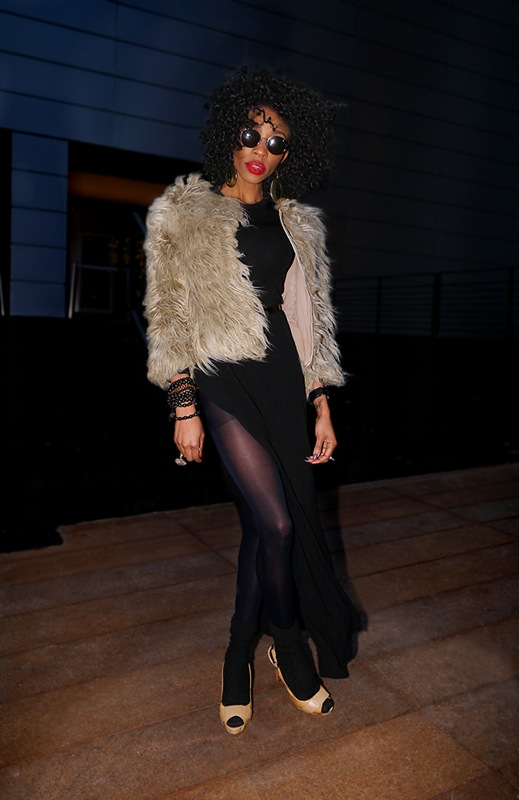 w long high slit black dress black stockings heels short fur jacket round sunglasses curly hair