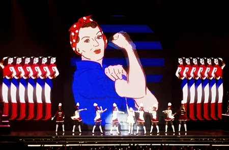 The-singer-and-her-troupe-are-dwarfed-by-an-image-from-the-1943-American-wartime-propaganda-poster-We-Can-Do-it