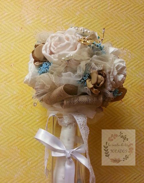 ramo realizado con flores en blanco roto, beige, dorado, azul...diferentes texturas como rasos, encajes, tul de novia y tul bordado, cinta de rafia, flores secas y broches y perlas