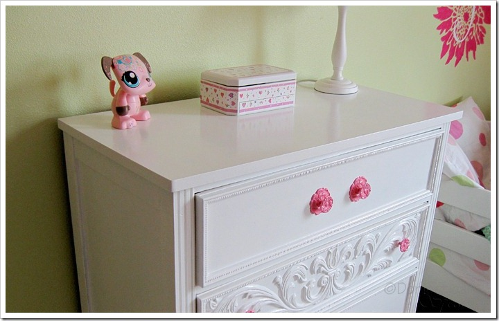 Pretty white dresser with pink knobs.