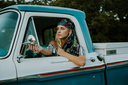 Young Blonde Woman Adjusting Wing Mirror by Averie Woodard