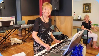 Events Manager, Diane Lyons, playing her Korg Pa900 whilst Margaret Black watches on whilst crewing the Entry Desk. Photo courtesy of Dennis Lyons.