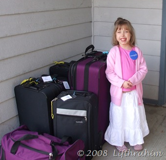 Supergirl with the luggage waiting for the shuttle.