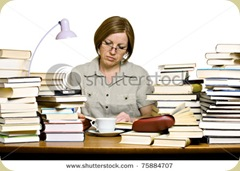 stock-photo-middle-aged-woman-sitting-behind-the-desk-reading-books-75884707
