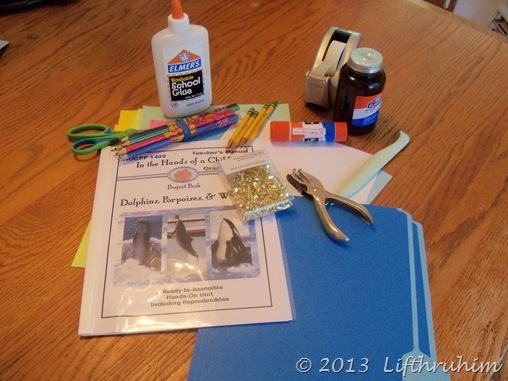 Picture of supplies needed such as bonefolder, file folder and glue
