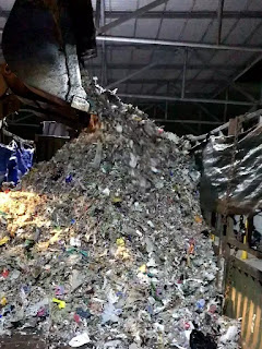 Rác hỗn hợp gồm thủy tinh, kim loại, bã giấy và các loại nilon được đưa lên thùng xe.