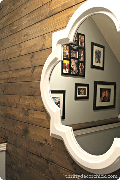 White mirror over wood wall