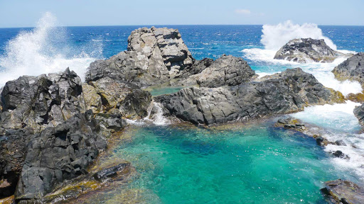 rocks-surf-Aruba - Rocky crags form a tidepool along the coast of Aruba.