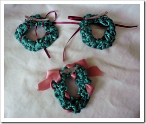 Crocheted ribbon Christmas wreaths.  These were used for hair clips and pins, but they would be cute for decorations.