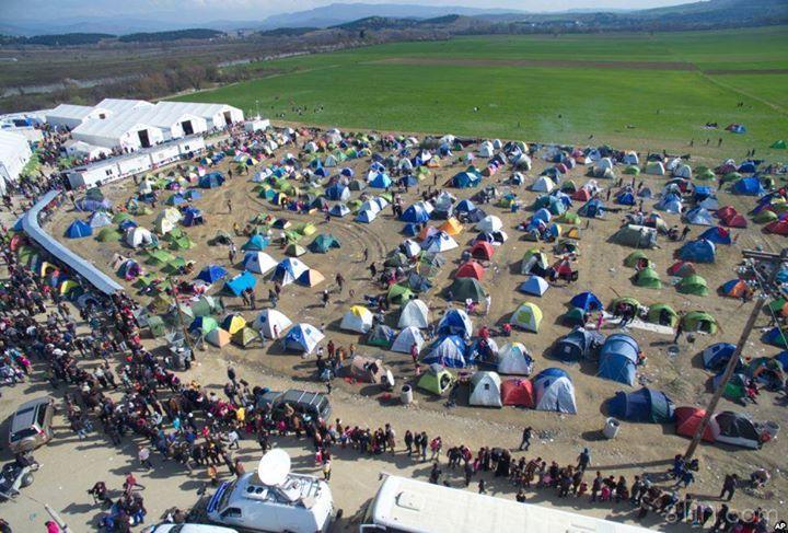 Người tị nạn và di dân chờ nhận thực phẩm do một
