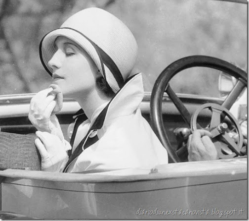 Actress Norma Shearer powdering her chin while sitting in the passenger seat of a car, 1929