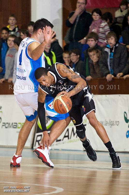 David Lawrence incearca sa treaca de Virgil Stanescu in timpul  partidei dintre BC Mures Tirgu Mures si U Mobitelco Cluj-Napoca din cadrul etapei a sasea la baschet masculin, disputat in data de 3 noiembrie 2011 in Sala Sporturilor din Tirgu Mures.