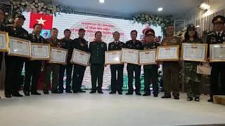 Đại tá Tạ Đức Thanh (Đoàn trưởng Đoàn 338, đứng giữa) trao huy hiệu cho các cán bộ, chiến sỹ