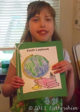 Supergirl proudly displays her Earth notebook
