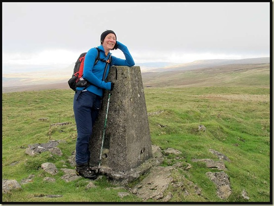 Heather reaches the trig point at 593 metres