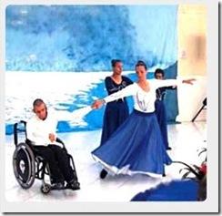 pessoa em cadeira de rodas participa de peça teatral ao lado de moça dançando em pé e segurando sua mão