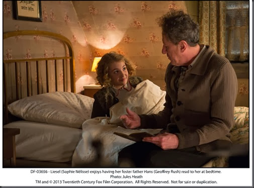 DF-03656 - Liesel (Sophie Nélisse) enjoys having her foster father Hans (Geoffrey Rush) read to her at bedtime.