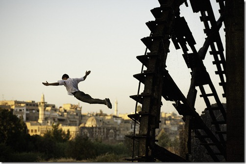 Street scene, Hama, Syria a man dives off of one of the famous noria (water wheels) in to the Orontes River.