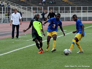 Sous les regards de deux entraineurs en arrière plan, à gauche de Lupopo, à droite de V. Club, les joueurs (V. Club en noire et lupopo en bleu) regardent un ballon tiré ce 22/05/2011, au stade des Martyrs à Kinshasa, lors dans le cadre de Vodacom Super Ligue dont le score final, 2 pour V. Club et 0 pour Lupopo. Radio Okapi/ Ph. John Bompengo