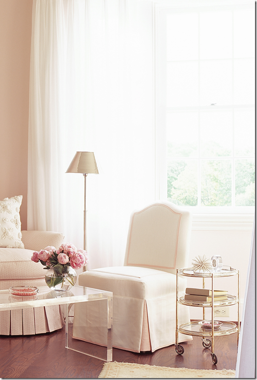 Gorgeous classic room design with blush pink walls, slipper chair, and acrylic coffee table. Design by Phoebe Howard. Come see the Best Sophisticated, Chic and Subtle Pink Paint Colors on Hello Lovely Studio!
