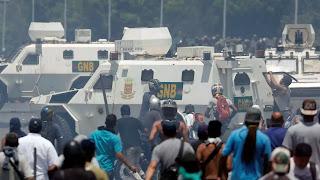 Người biểu tình đang xung phong xáp lá cà với xe thiết giáp của chế độ độc tài.
