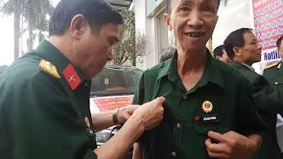 Cựu chiến binh Đỗ Xuân Trường được đồng đội cũ giúp đeo huy hiệu