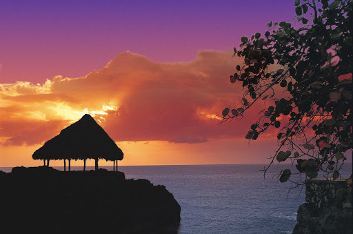 sunset-over-hut-in-Jamaica - A hut is framed against an orange sunset in Jamaica.