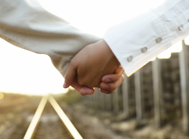 Couple Holding Hands on a Railroad Track --- Image by © Royalty-Free/Corbis