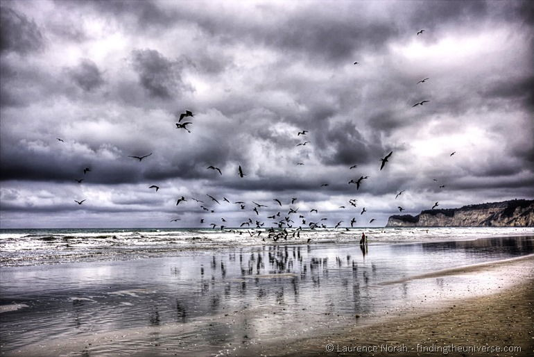 Frigate birds on beach Canoa people standing clouds