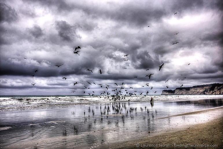 Frigate birds on beach Canoa people standing clouds