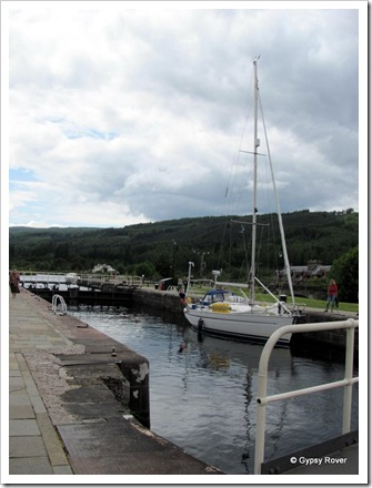 A lone yacht going down the Caledonian canal flight at Fort Augustus.