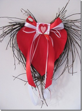 Red felt heart wreath with red ribbon bow.
