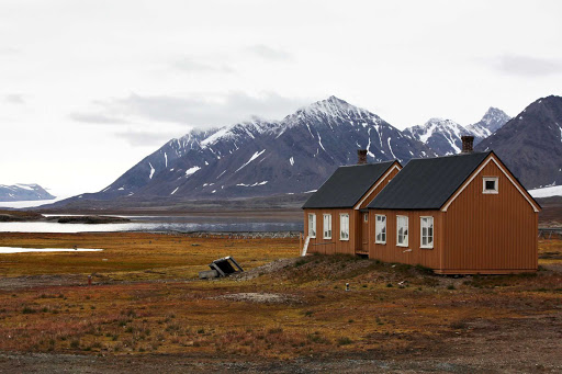Svalbard-mountains-and-house - Revel in the peacefulness of the Svalbard Islands as you explore the region aboard the Hurtigruten Fram.