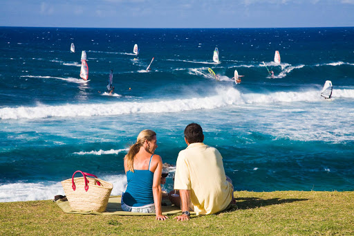 windsurfers-Maui - A couple enjoys a picnic while watching windsurfers in Lower Paia, Maui.