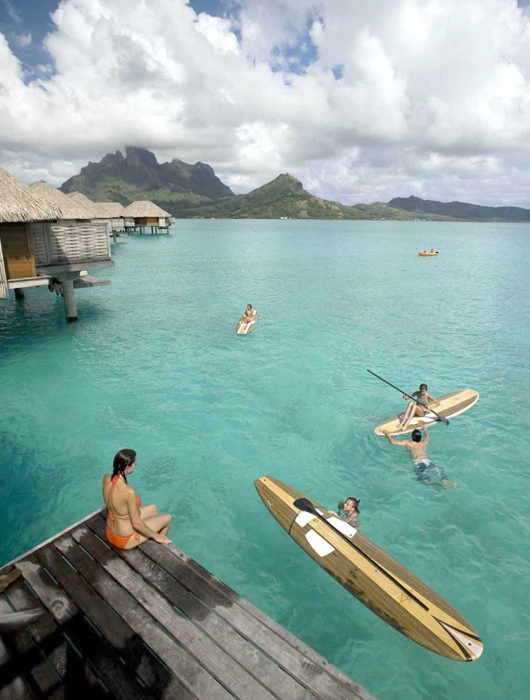 Recreation options include stand-up paddle boarding at the Four Seasons Resort Bora Bora.