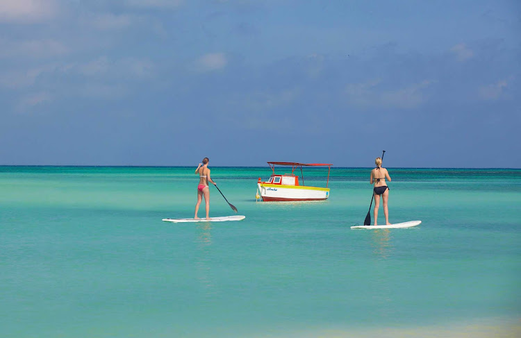 Two women on stand-up paddleboards in Aruba.
