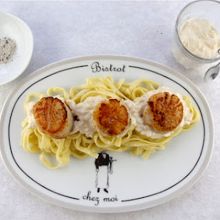 SCALLOPS IN CHAMPAGNE CREAM SAUCE WITH TRUFFLE SALT.