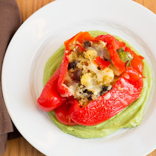 Stuffed Red Bell Peppers with Couscous and Avocado Sauce.