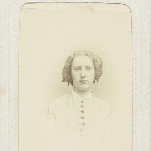 923bf6c889e2fa Studioportret van een vrouw in een hooggesloten jurk en pijpenkrullen in  het haar