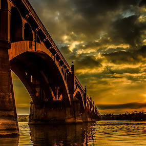 Crossing into Sunset by Troy Snider - Buildings & Architecture Bridges & Suspended Structures ( water, sparkling, sunset, arches, stone, road, bridge, river crossing, river )