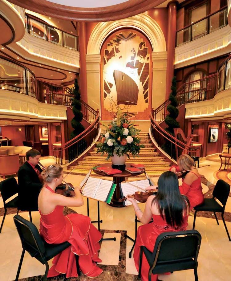 A string quartet performs in the Grand Lobby of the Queen Elizabeth, which reaches three decks high.