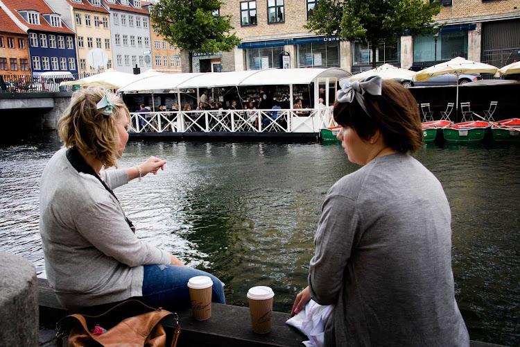Two local women take a break at a canal in Copenhagen.