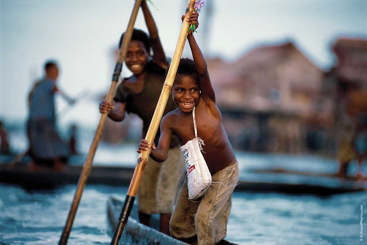 Two boys on the Sepik River in Madang, Papua New Guinea. Take part in local traditions when you sail the South Seas with Silver Discoverer.