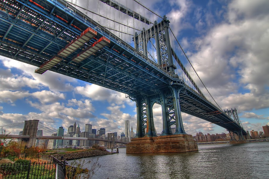 DUMBO by David McBride - Buildings & Architecture Bridges & Suspended Structures ( water, clouds, brooklyn bridge, grass, green, under, architecture, new york, nyc, fence, red, sky, financial district, manhattan bridge, blue, bridge, brooklyn )