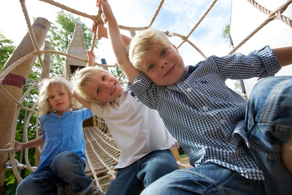 Du siehst ein Mädchen und zwei Jungen im Seilenetz spielen