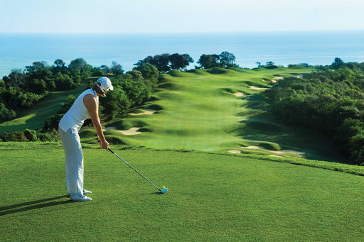 Seeing green: A woman is about to tee off on a golf course hugging the Jamaican coast.